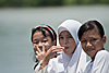 Girls in White (Kinabatangan River Part I) Photo: Three young Malaysian children ride the school-boat on the Kinabatangan River after a long day of classes.