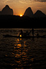 Sunrise (Karsts IV) Photo: A tourist rides on a traditional flat bamboo boat with karsts as a backdrop.