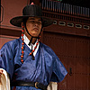 photo: Gatekeepers - A guard carrying the royal flag stands aside the main entrance to Gyeongbokgung Palace.