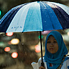 Rainy Day Blues (& Pinks) Photo: A Muslim woman remains dry during a typical Malaysian downpour.