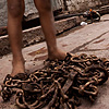 Metal Worker Photo: A young boy takes a break from repeatedly lifting and dropping a set of chains.