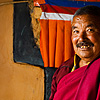 photo: Brawn & Wall - A Buddhist monk poses in front of a colorful wall.