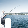 Flush Fisherman Photo: A Swiss man fishes from a boat dock into Lake Geneva.