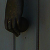 Limp Limb Photo: A metal hand grasping a ball swing on a hinge for a door knocker.