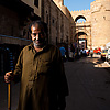 Kind Caned Character Photo: A Egyptian man stands with a cane in front of the Bab Zuweila gateway.