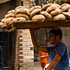 photo: Starch Source - A bicycle bread delivery guy carries a rack of fresh bread on his head.
