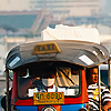 Traditional Taxi Photo: An air-polluting tuk-tuk heads outbound from downtown Bangkok.