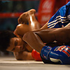 Muay Thai Action Photo: Entangled muay thai kickboxers fall to the canvas ending up in awkward positions.