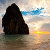Railay Beach Mountain Photo: A gentle waves breaks on the shore at sunset in front of a large limestone mountain on Phranong Beach.