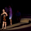 photo: Female Thai Violinist - A Thai violinist reacts to an audience member at an open-air show in Bangkok.