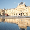 Museum Middle (panorama) Photo: The facade of the Louvre and glass pyramid reflected in a water fountain in the museum's courtyard.