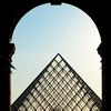 Louvre Leave Photo: People walk through an archway into the courtyard of the Louvre museum.
