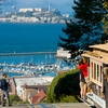 Peak & Prison Photo: The Hyde Street cable car descends at its peak with Alcatraz Prison in the background.
