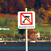 "Swimming Sign Photo: A ""Swimming Forbidden"" sign warns visitors at the end of a pier on Annecy Lake."